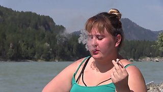 Beautiful fat woman smoking on the river bank